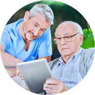 caregiver and old man browsing internet using tablet device