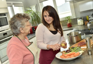 caregiver cooking dinner for elderly woman
