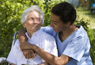 caregiver hugging senior from behind
